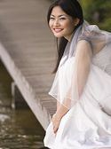 A beautiful asian bride sits on a boardwalk at the edge of a lake