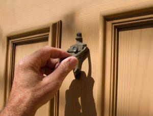 hand on brass door knocker